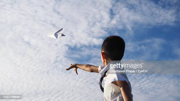 side view of boy flying paper airplane against sky - paper airplane stock pictures, royalty-free photos & images