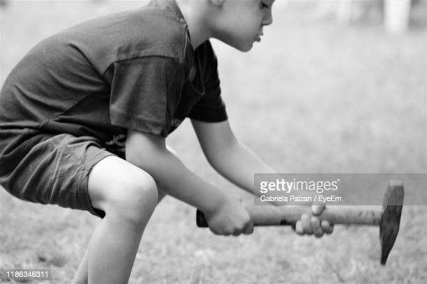 side view of boy holding tool on land - gabriela stock pictures, royalty-free photos & images