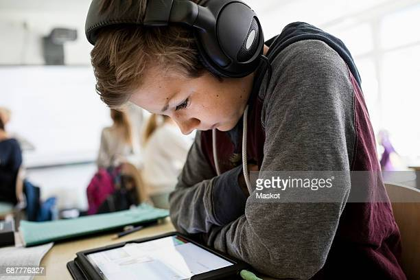 Side view of boy listening to headphones while using digital tablet in classroom
