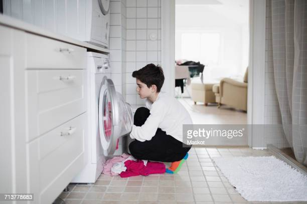 Side view of boy loading washing machine while crouching at home