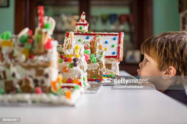 Side view of boy looking at gingerbread houses