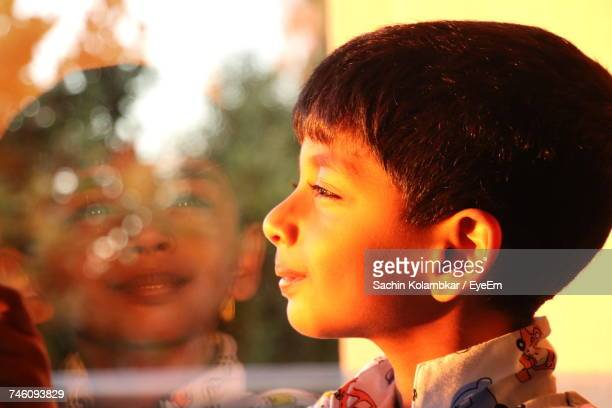 Side View Of Boy Looking Through Window