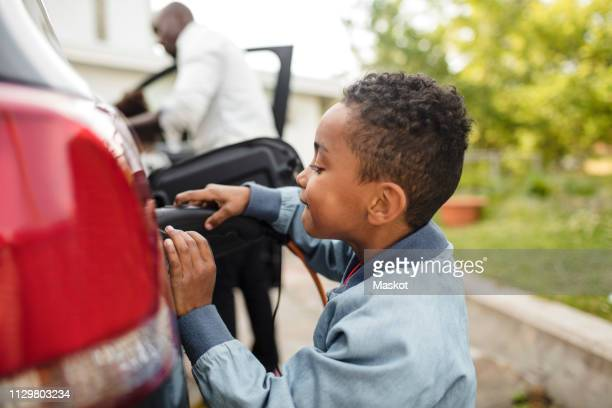 side view of boy looking while charging electric car - elektroauto stock-fotos und bilder