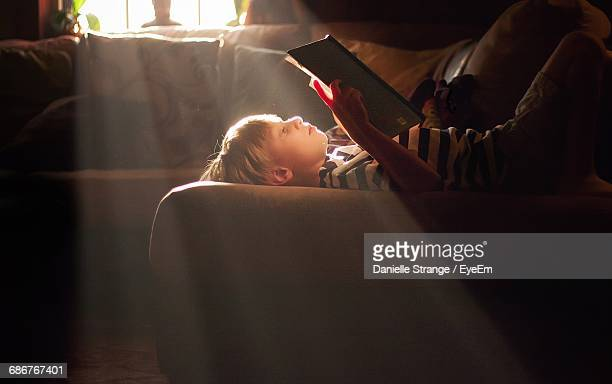 side view of boy lying on sofa reading book at home - alleen jongens stockfoto's en -beelden