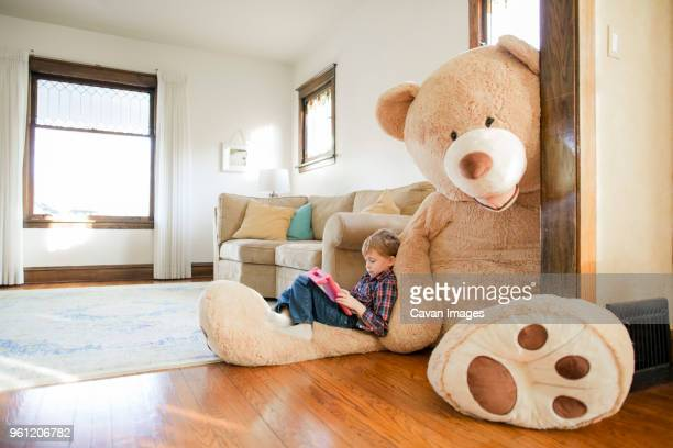 side view of boy playing game while sitting on large teddy bear at home - large stock pictures, royalty-free photos & images