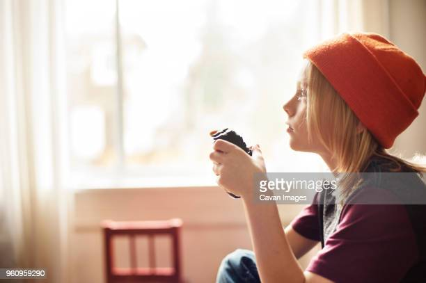 Side view of boy playing video game at home