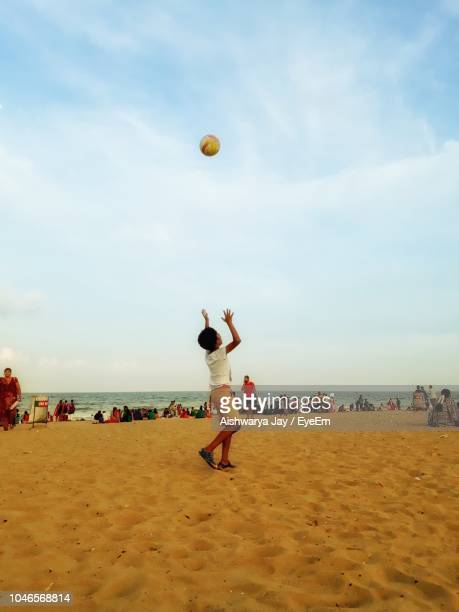 Side View Of Boy Playing With Ball While Standing At Beach Against Sky