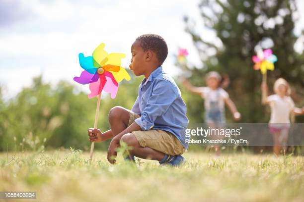 side view of boy playing with pinwheel toy at park - paper windmill stock photos and pictures
