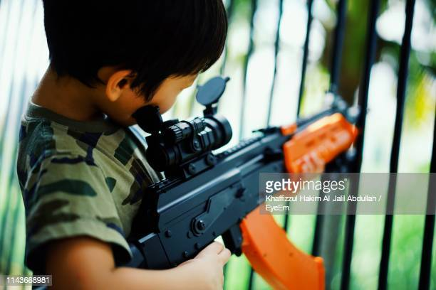 side view of boy playing with toy gun - weaponry stock pictures, royalty-free photos & images