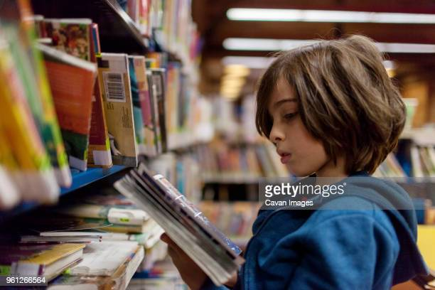 Side view of boy reading comic book in library