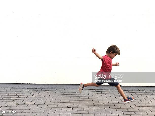 Side View Of Boy Running On Footpath Against White Wall