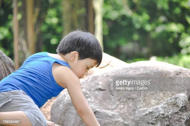 Side View Of Boy Sitting By Rock
