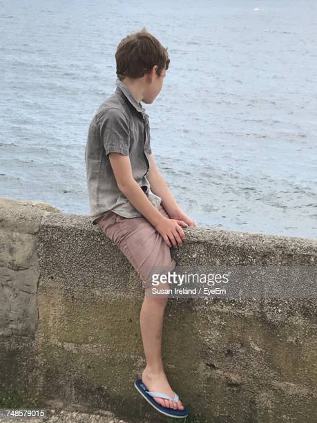 Side View Of Boy Sitting On Retaining Wall By Sea