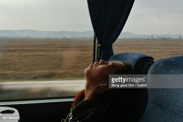 Side View Of Boy Sleeping While Sitting By Window In Train