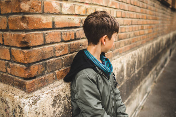 Side View Of Boy Standing Against Wall