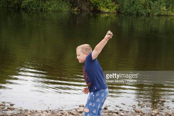side view of boy standing at lakeshore - carlisle stock pictures, royalty-free photos & images