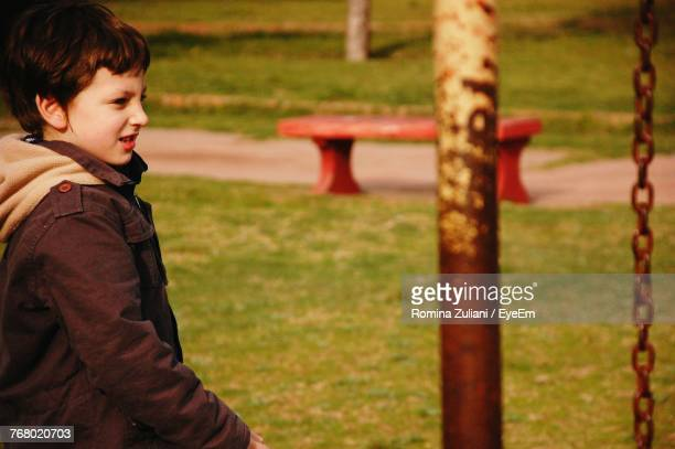 Side View Of Boy Standing At Park