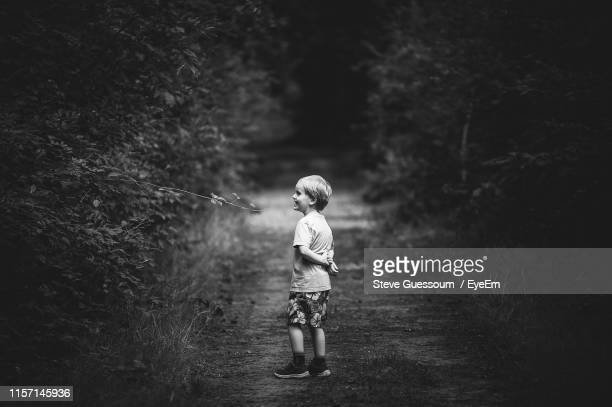 side view of boy standing on field by plants - steve guessoum stockfoto's en -beelden