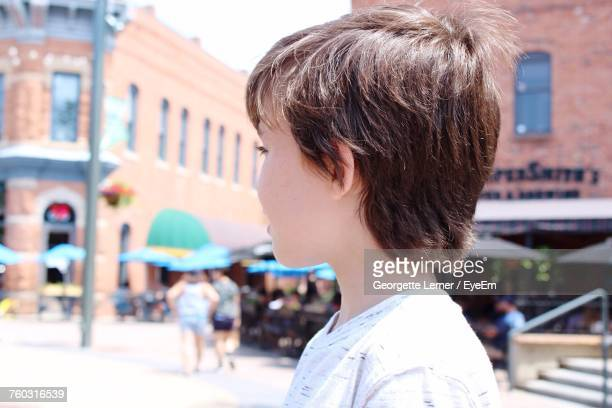 side view of boy standing on street during sunny day - fort collins stock pictures, royalty-free photos & images