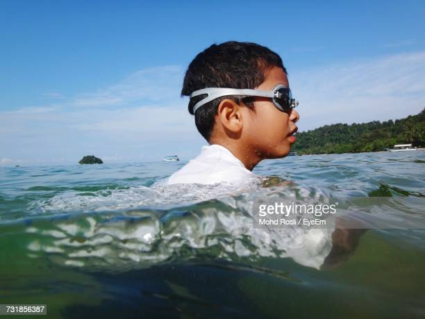Side View Of Boy Swimming In Sea Against Sky