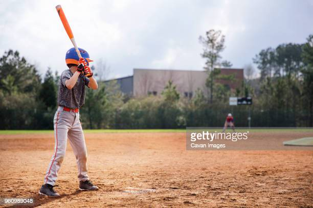 side view of boy swinging baseball bat on field - batting sports activity stock pictures, royalty-free photos & images