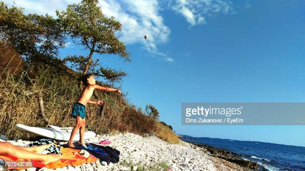Side View Of Boy Throwing Stone While Standing On Shore At Beach