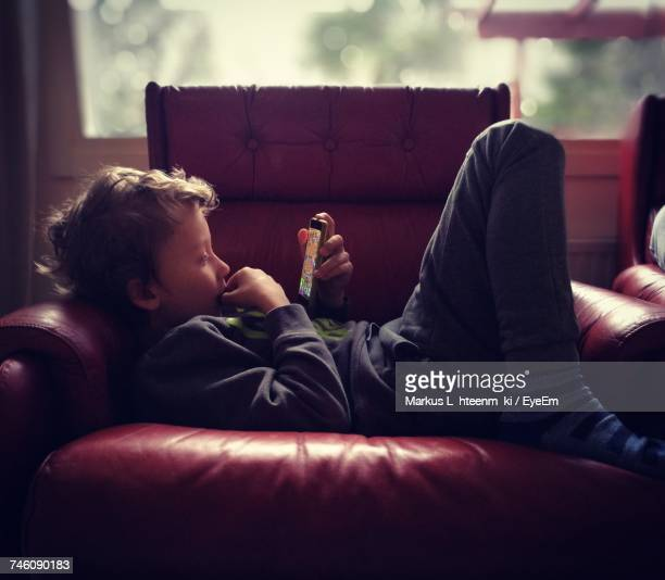Side View Of Boy Using Smart Phone While Lying On Armchair
