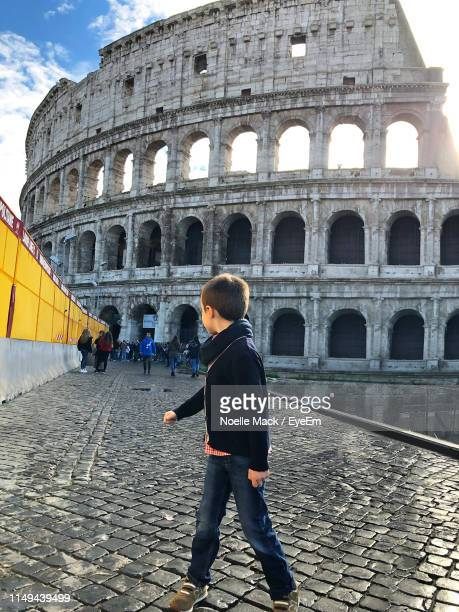 side view of boy walking by coliseum - mack stock pictures, royalty-free photos & images