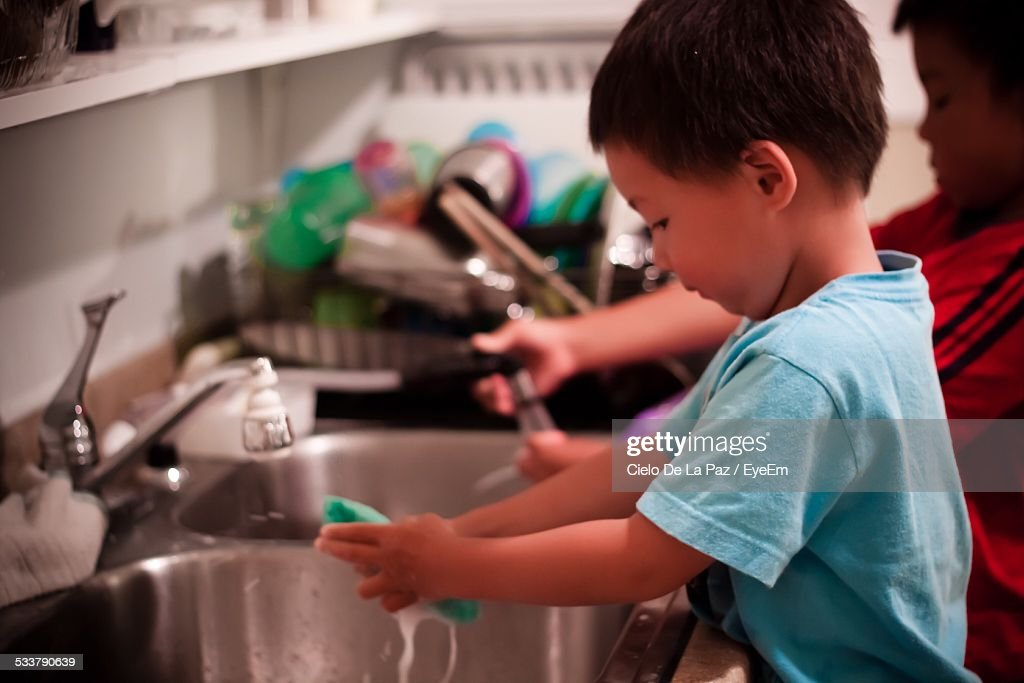 Side View Of Boy Washing Dishes At Kitchen Sink : Foto stock