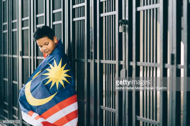 side view of boy wearing malaysian flag by fence - malaysian culture stock pictures, royalty-free photos & images