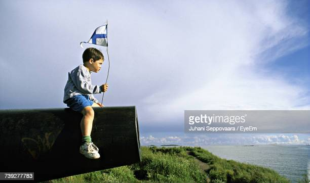 Side View Of Boy With Finnish Flag Sitting On Cannon Against Sky