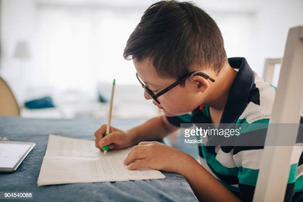 Side view of boy writing on book while sitting at table