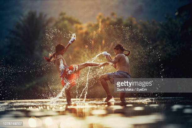 side view of boys fighting in water - aggression stock pictures, royalty-free photos & images