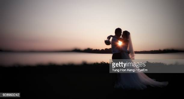 Side View Of Bride And Groom Embracing By Lake At Sunset