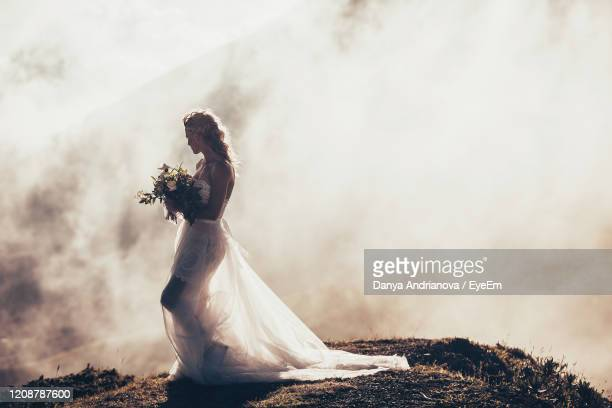 side view of bride holding bouquet standing outdoors - materia foto e immagini stock