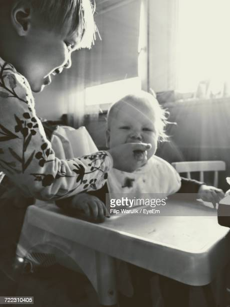 Side View Of Brother Feeding Baby Girl Sitting On High Chair