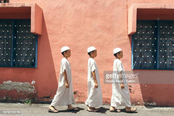 side view of brothers in traditional clothing walking by building - スカルキャップ ストックフォトと画像