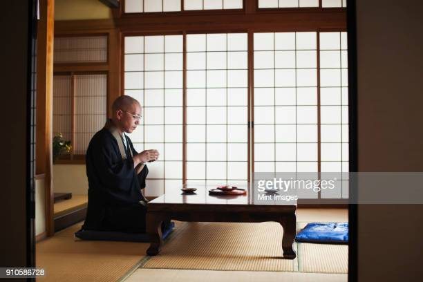 side view of buddhist monk with shaved head wearing black robe kneeling indoors at a table, holding bowl of tea. - 僧 ストックフォトと画像