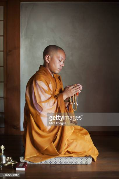 side view of buddhist monk with shaved head wearing golden robe kneeling indoors in a temple, holding mala, praying. - shingon buddhismus stock-fotos und bilder