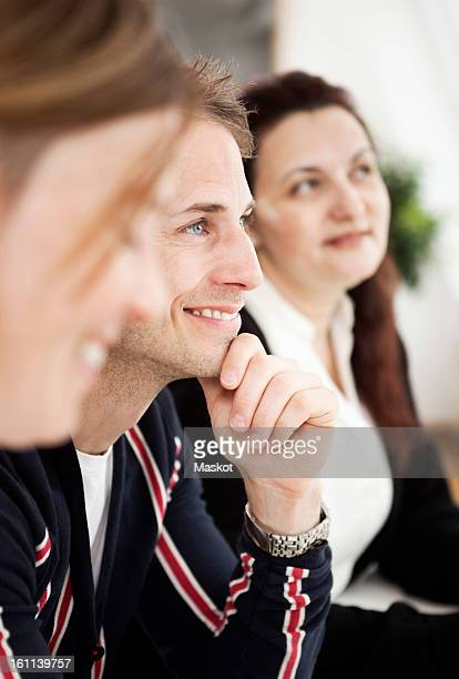 side view of business colleagues in seminar with focus on man smiling - bijwonen stockfoto's en -beelden
