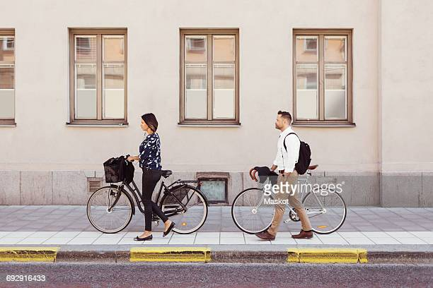 Side view of business colleagues walking with bicycles on sidewalk