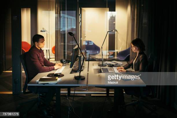 Side view of business colleagues working at desk in dark office