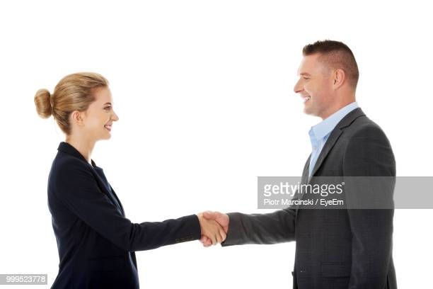 Side View Of Business People Shaking Hands Against White Background