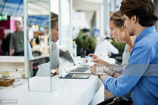 Side view of business people using credit card and laptop at airport lobby