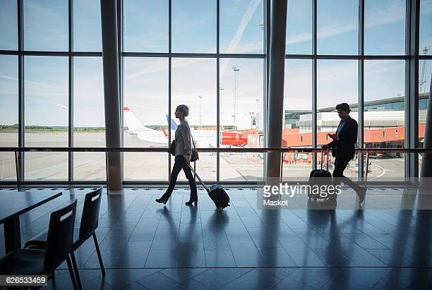 Side view of business people walking with luggage at airport