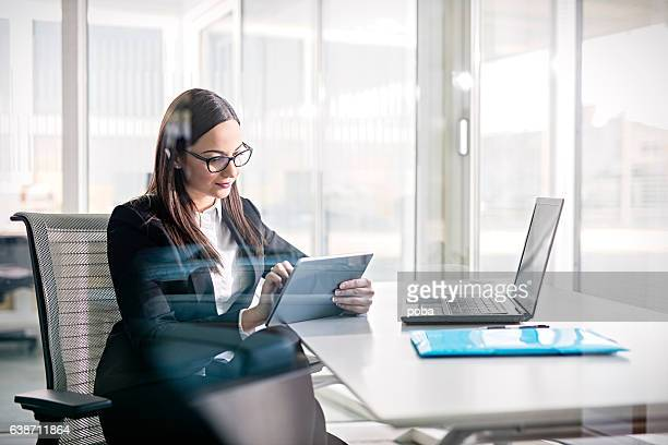 Side view of business woman working on digital tablet