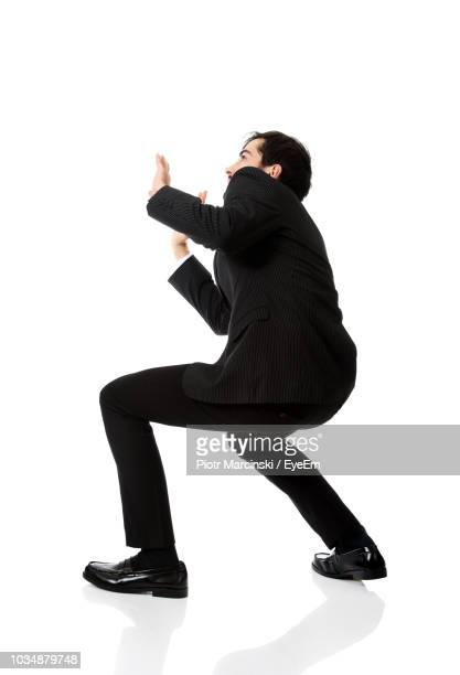 Side View Of Businessman Bending Against White Background