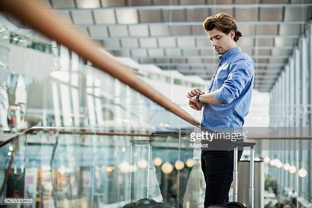 Side view of businessman checking the time while standing by glass railing at airport