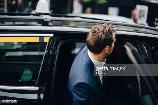 side view of businessman entering taxi in city - taxi fotografías e imágenes de stock