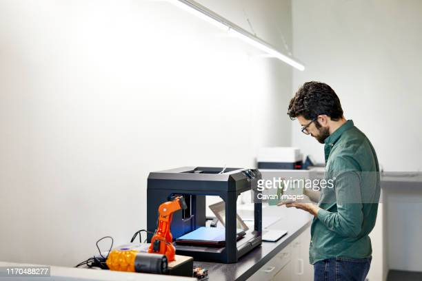 side view of businessman examining model while standing by 3d printer in office - 3d printing stock pictures, royalty-free photos & images